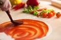Italian pizza preparation adding sauce Stock Image