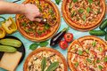 Italian pizza set at blue wooden background. chef cuts pizza. italian cuisine. gourmet pizza collection