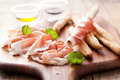 Italian prosciutto ham grissini bread sticks olive oil olives Stock Photo