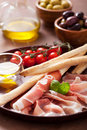 Italian prosciutto ham grissini bread sticks tomato olive oil olives Royalty Free Stock Photos