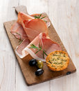 Italian prosciutto or parma ham in thin gourmet slices garnished with fresh rosemary and served with olives and golden toasted Stock Photo