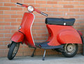 Italian red vespa scooter vintage near a brick wall Stock Image