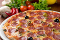 Italian salami pizza on table with vegetables Royalty Free Stock Photos