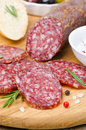 Italian salami sliced ​​into pieces on wooden cutting board a close up vertical Stock Image