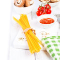 Italian spaghetti, champignon, dry mushrooms, tomato sauce, fresh cherry tomatoes, and spices on a wooden background, pasta ingred Royalty Free Stock Photo