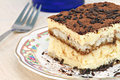 Italian tiramisu cake macro with selective focus on edge one slice of forward an antique beautiful plate Stock Image