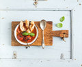 Italian tomato, garlic and basil soup Pappa al Pomodoro in metal bowl with bread on rustic wooden board over light blue Royalty Free Stock Photo