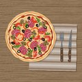 Izza on wooden background. There is also a knife and fork on a napkin Royalty Free Stock Photo