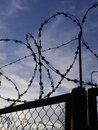 Silhouette of a fence with barbed wire against a blue sky. Prison security. Royalty Free Stock Photo