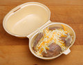 Jacket or baked potato with cheese grated in foam takeaway box sharp focus on grated Stock Photos