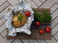 Jacket potato from the braai wrapped in tinfoil with cherry tomato red pepper flakes garlic butter and parsley Royalty Free Stock Images