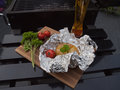 Jacket potato dinner from the braai wrapped in tinfoil with cherry tomato red pepper flakes garlic butter and parsley Stock Photography