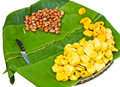 Jackfruit seeds with a kitchen knife split apart and placed on banana leaves in a pannier Stock Image