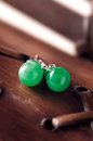 Jade earrings a pair of on wood Royalty Free Stock Photos