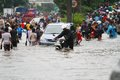 Jakarta flood people motorcycles and cars crossing the in Royalty Free Stock Images