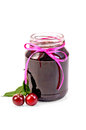 Jam cherry in a glass jar two cherries on branch with leaves with light shade on white background Stock Photography