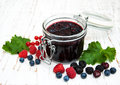 Jam and fresh berries on a wooden background Royalty Free Stock Photo