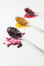 Jam mixed berry apricot and sour cherry on spoons Stock Image