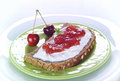 Jam sandwich on green plate garnishes with mint and cherries on the edge of the plate Royalty Free Stock Images