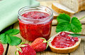 Jam strawberry with bread on the board in a glass jar leaves napkin knife background wooden plank Royalty Free Stock Photography