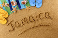Jamaica beach writing the word written on a sandy with seashells towel starfish and flip flops Royalty Free Stock Image