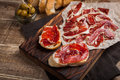 Jamon Iberico with white bread, olives on toothpicks and fruit on a wooden background. Top view Royalty Free Stock Photo