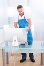 Janitor or cleaner cleaning an office handsome young spraying the top of the desk with disinfectant before the workers Stock Images