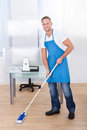 Janitor cleaning the floor in an office building Royalty Free Stock Photo