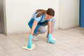 Janitor cleaning floor with rag female wearing gloves Royalty Free Stock Photography