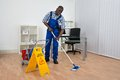 Janitor cleaning floor with wet floor sign young happy Royalty Free Stock Photo