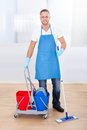 Janitor cleaning wooden floors with a mop and a cart with two buckets for the disinfectant and water pausing to smile at the Royalty Free Stock Photo