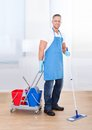 Janitor cleaning wooden floors with a mop and a cart with two buckets for the disinfectant and water pausing to smile at the Royalty Free Stock Photography