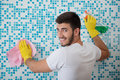 Janitor depriving you from dirt half length portrait of young smiling dark haired wearing white shirt and yellow rubber gloves Stock Image