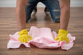 Janitor depriving you from dirt selected focus on the hands of wearing yellow rubber gloves scrubbing floors with the pink duster Royalty Free Stock Images