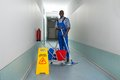 Janitor holding mop with bucket and wet floor sign young happy in corridor Royalty Free Stock Images