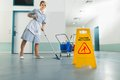 Janitor with mop and wet floor sign happy female on Stock Image