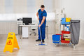Janitor Mopping Floor In Office Royalty Free Stock Photo