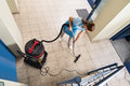 Janitor vacuuming floor high angle view of young female Royalty Free Stock Images