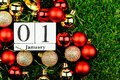 01 january alphabet and red christmas ball on wooden calendar block on green grass.