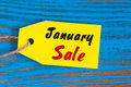 January Sale, price tag on blue wooden background Royalty Free Stock Photo
