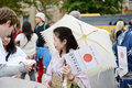 Japanese charity worker female in traditional costume of kimono helping for orphans at matsuri festival Stock Image