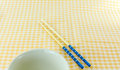 Japanese chopsticks and bowl on yellow fabric Royalty Free Stock Photo
