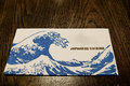 Japanese cuisine a placemat with breaking waves sits on a table top Royalty Free Stock Image