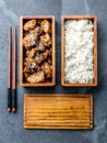 Japanese food. Chicken teriyaki with rice in wooden bento lunch box. slate background, top view. Royalty Free Stock Photo
