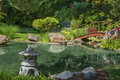 Japanese garden beautiful manicured with mature maple pine and juniper trees surrounding an ornamental koi pond with a Stock Photos