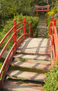 Japanese garden detail in the spring small bridge leading towards a gate Royalty Free Stock Photo
