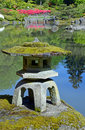 Japanese garden pond rock lantern on rock in reflective in botanical Stock Image