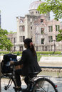 Japanese girl hiroshima peace memorial atomic bomb dome japan july a is cycling past the aka that was destroyed by the Stock Photos