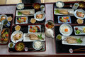 Japanese homestay breakfast tray including cooked white rice, grilled fish, fried egg, tofu soup, sausage, pickle, seaweed, etc. Royalty Free Stock Photo