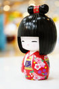Japanese kimono smiling doll the black hairs which wears the red with flowers pattern Royalty Free Stock Image